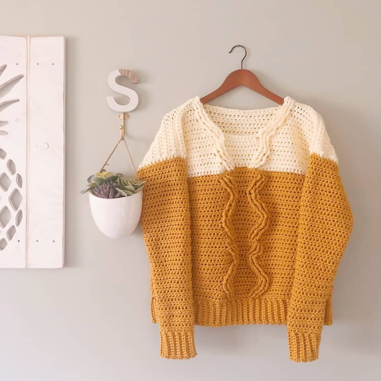 mustard and cream crochet cable sweater on hanger against grey wall with potted plant