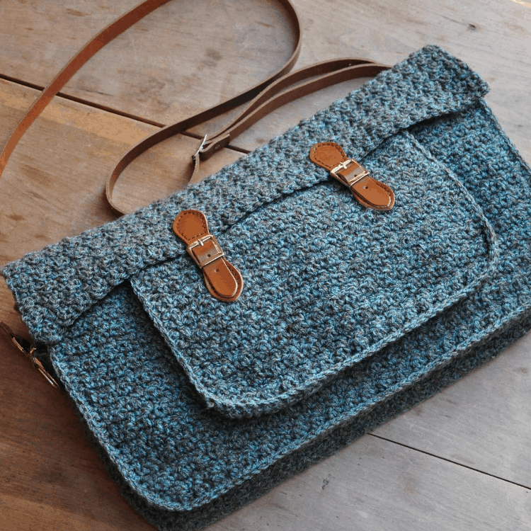 blue tweed messenger satchel bag with brown leather straps on wooden table