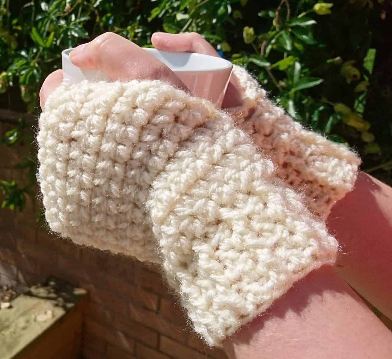 cream crochet wrist warmers holding cup of coffee