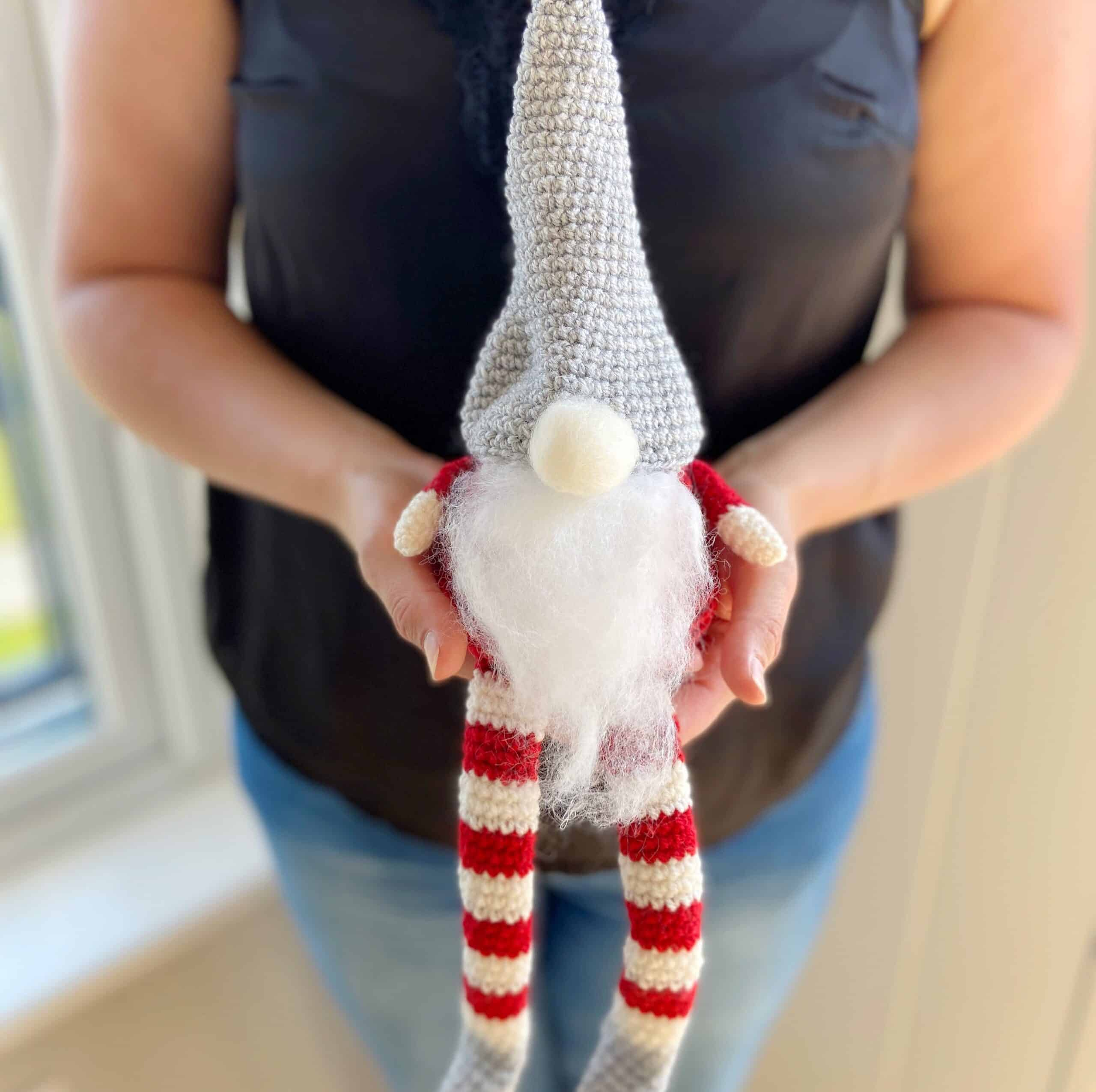 Christmas crochet gnome in red, white and grey being held by woman in hands