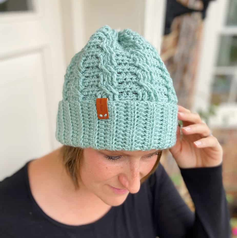 woman wearing mint green crochet cable hat touching the brim with her fingers