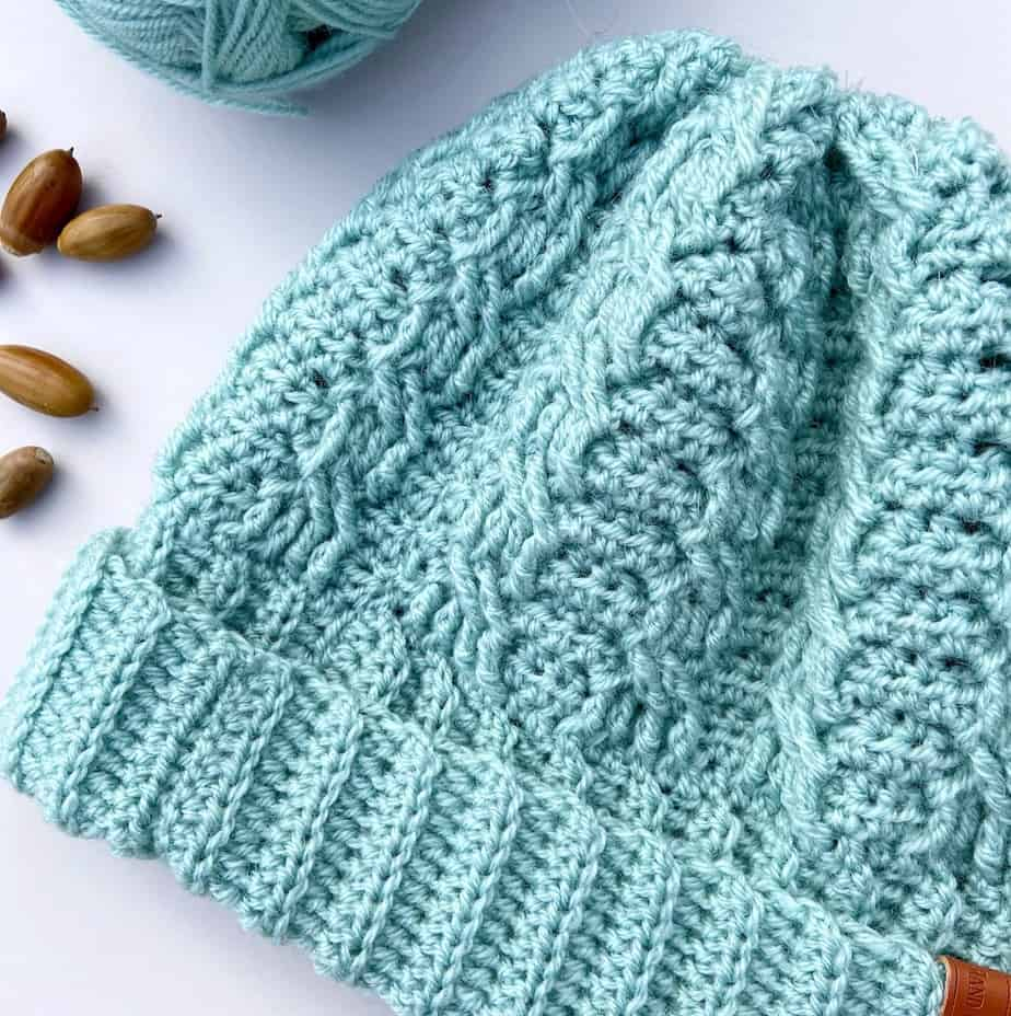 close up of mint green crochet cable hat with wide brim laid on table with crochet hook and acorns
