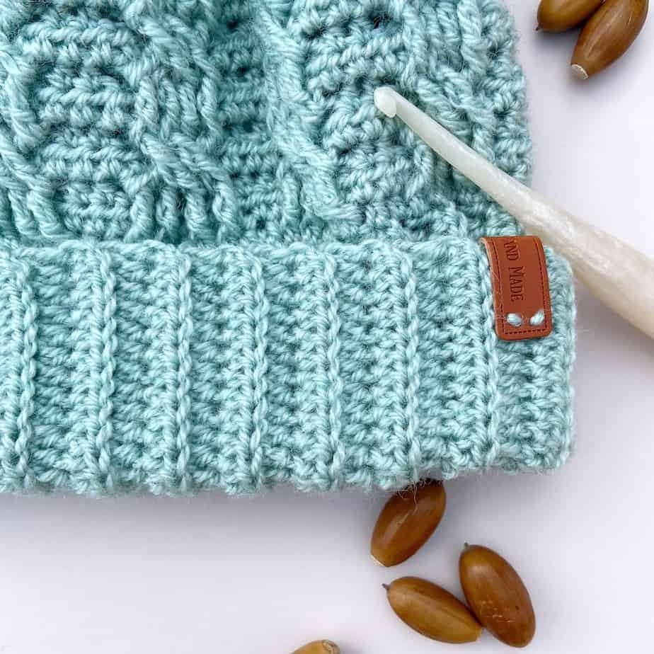 close up of mint green crochet cable hat with crochet hook and acorns laying on table