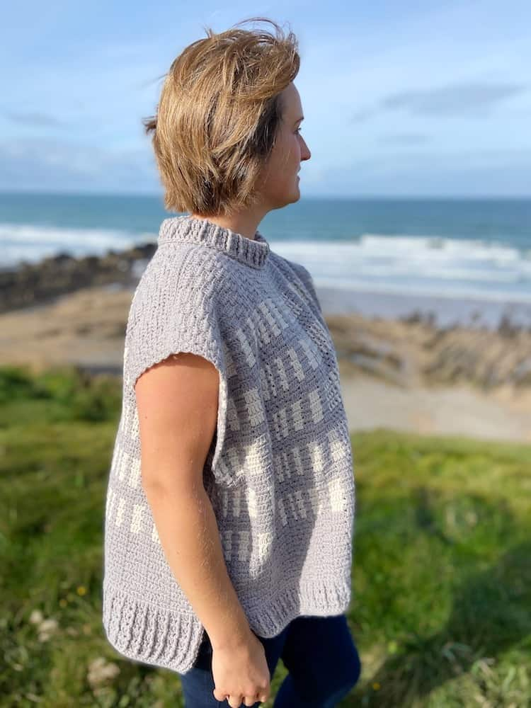 woman standing on cliff top wearing grey and white crochet poncho with hair blowing in the wind