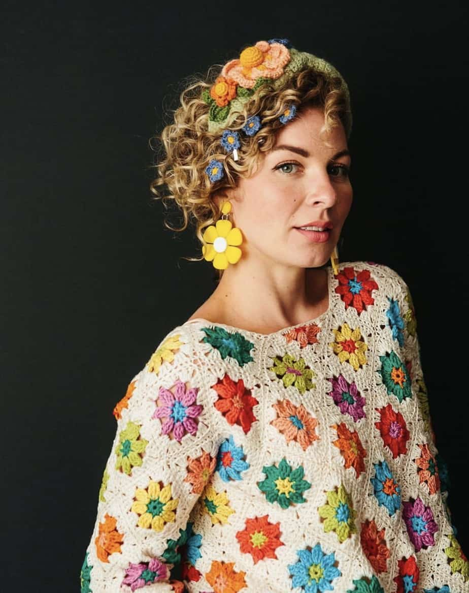 woman with short curly hair wearing bright flower motif crochet jumper and large yellow daisy earrings