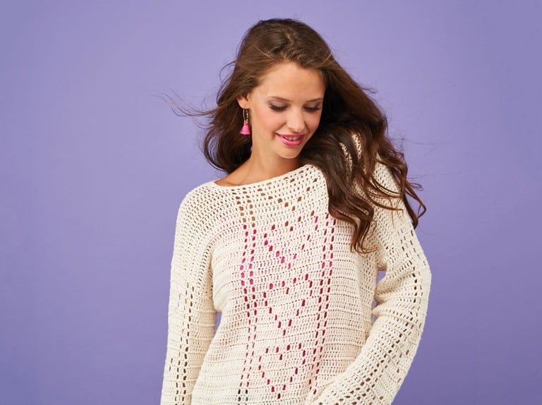 woman with long hair wearing cream filet crochet jumper with hearts on
