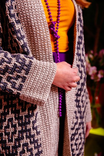 woman wearing purple and cream mosaic crochet cardigan