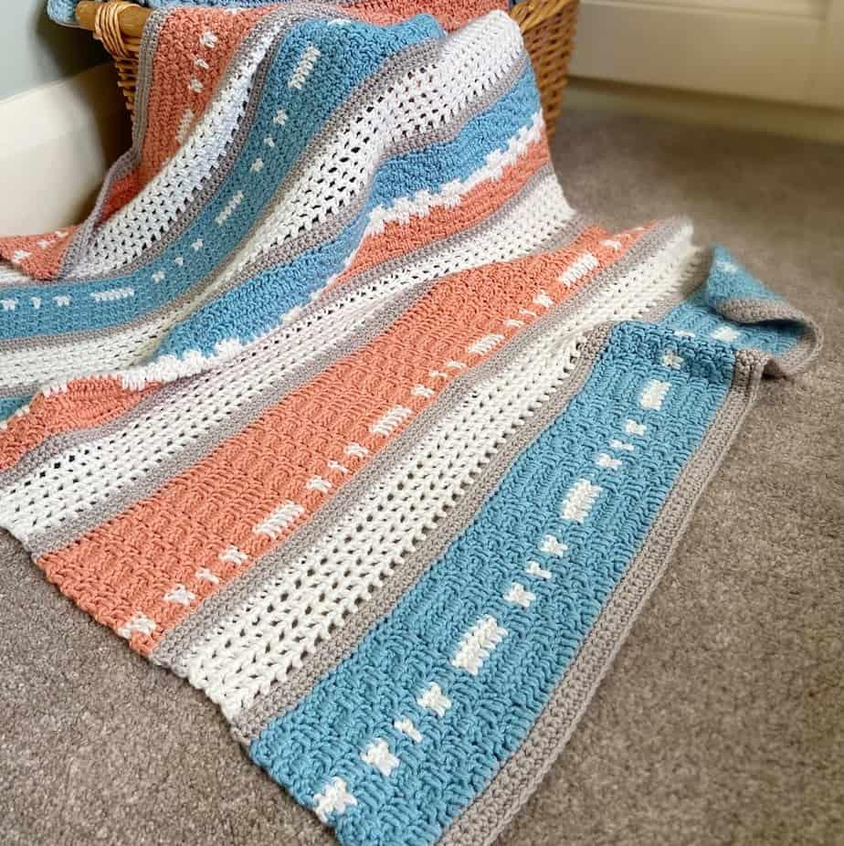 modern crochet baby blanket draped over a basket on the floor