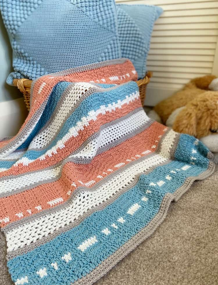 modern peach and teal crochet baby blanket draped over basket with cushions and cuddly toy