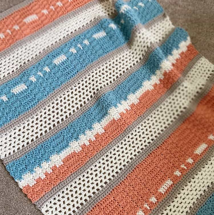 modern crochet blanket for babies in peach and teal laying on floor