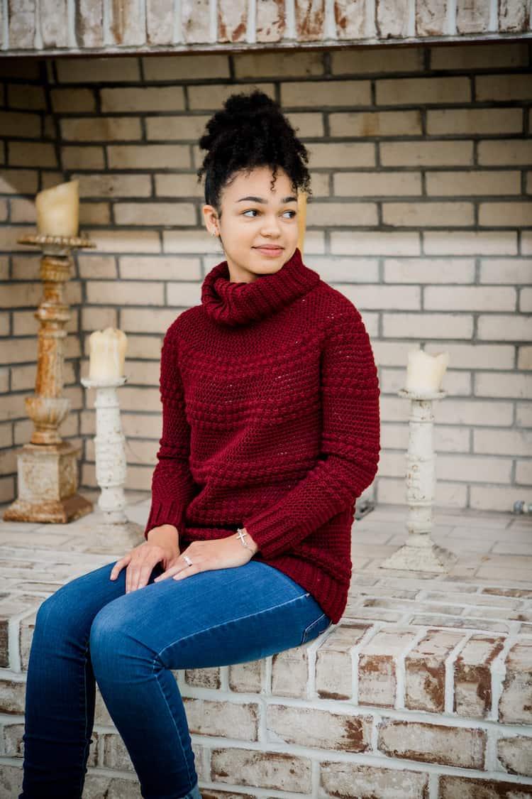 woman sitting wearing cranberry biscotti turtleneck crochet foundry sweater