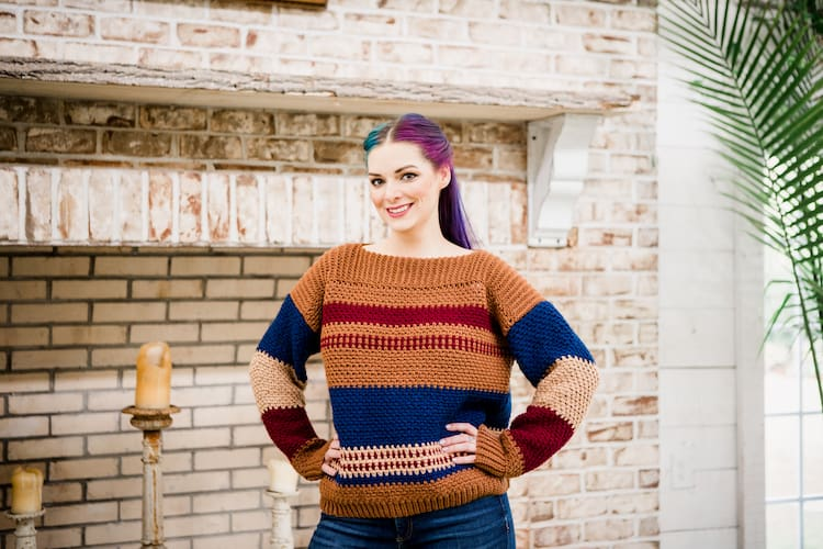woman with blue and pink hair wearing crochet gingerbread pullover jumper
