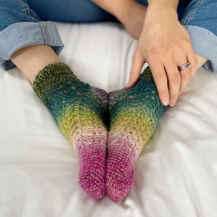 ombre lacy crochet socks being worn with feet together and hand holding ankle