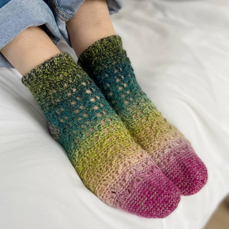 feet wearing ombro crochet socks with toes pointing down and denim jeans