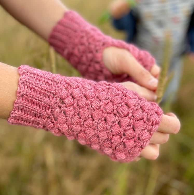 textured pink puff stitch crochet mittens being worn with hands outstretched and little boy playing in background