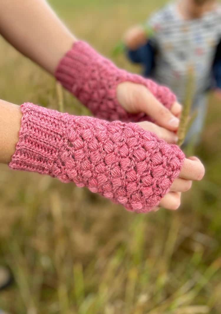 close up of hands wearing pink puff stitch crochet mittens with little boy playing in the background