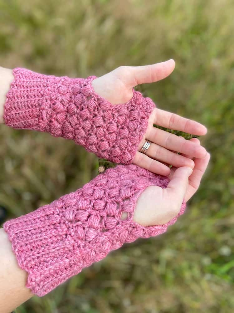 close up of hands holding palms open wearing pink puff stitch crochet mittens