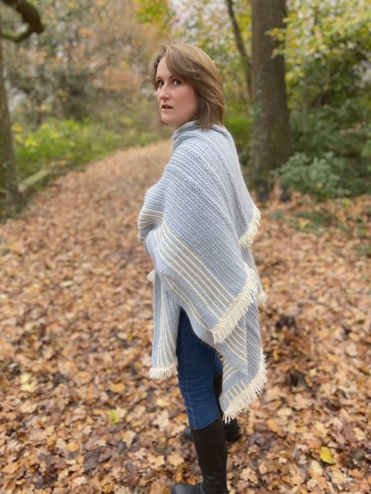 woman looking back over her shoulder in woodland wearing braided blanket crochet ruana