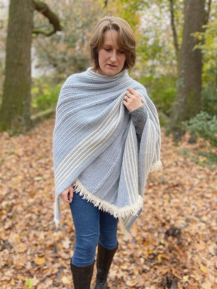 woman in woods wearing jeans, boots and crochet wrap like a blanket