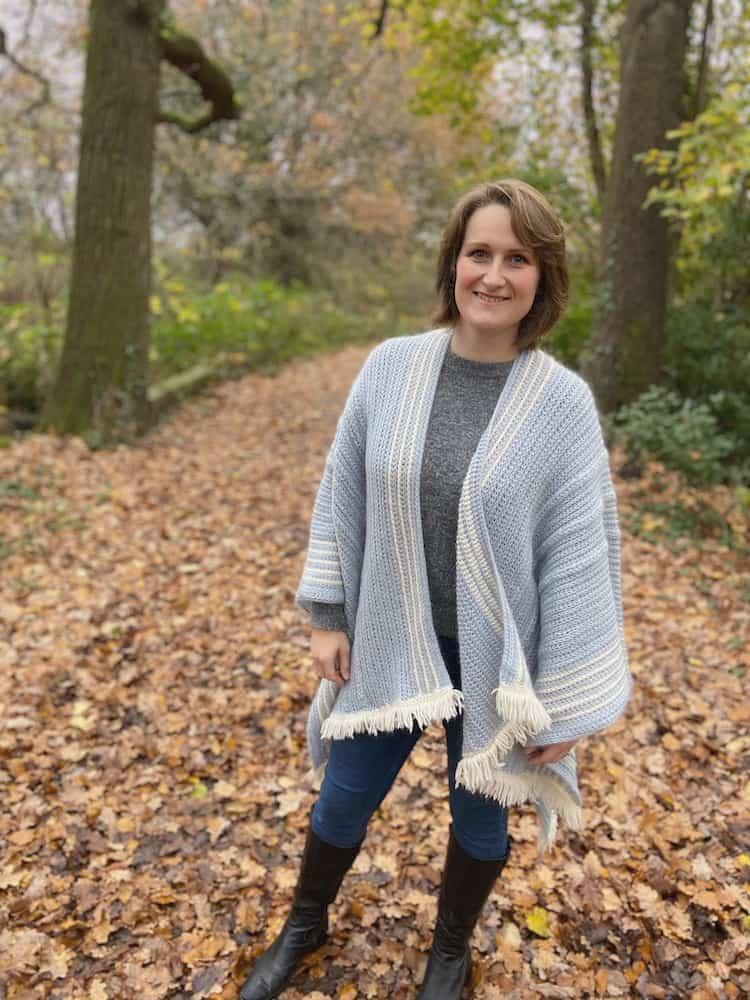 woman in woods smiling wearing braided blanket crochet ruana