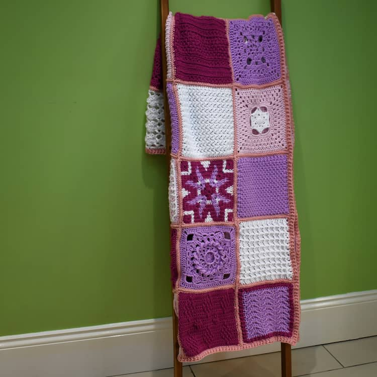 friendship CAL crochet blanket displayed on ladder leaning against a wall