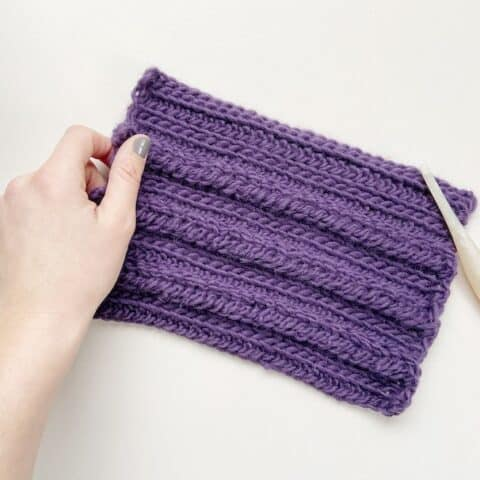 crochet braid stitch swatch with crochet hook and hand