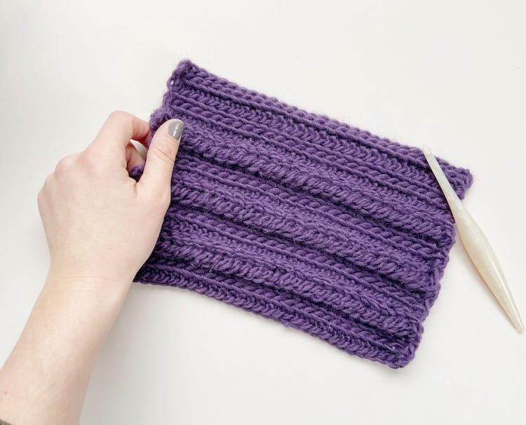 hand holding crochet braid stitch swatch in purple yarn