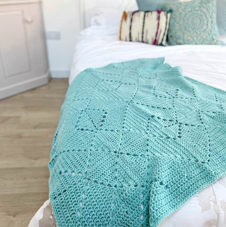 teal coloured crochet granny blanket laid on bed with white sheets