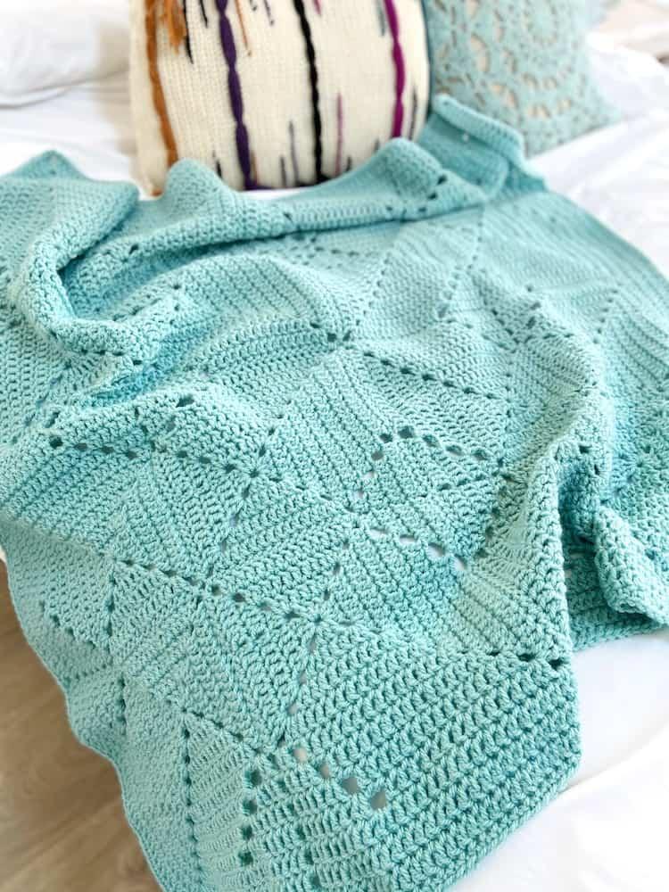 pale teal crochet blanket on bed