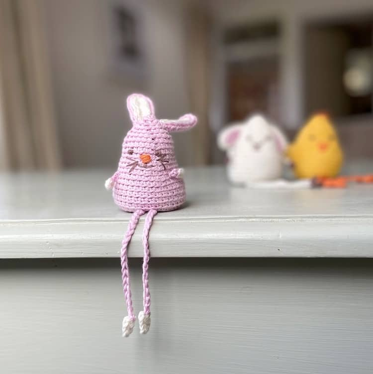 amigurumi crochet bunny sitting on edge of shelf