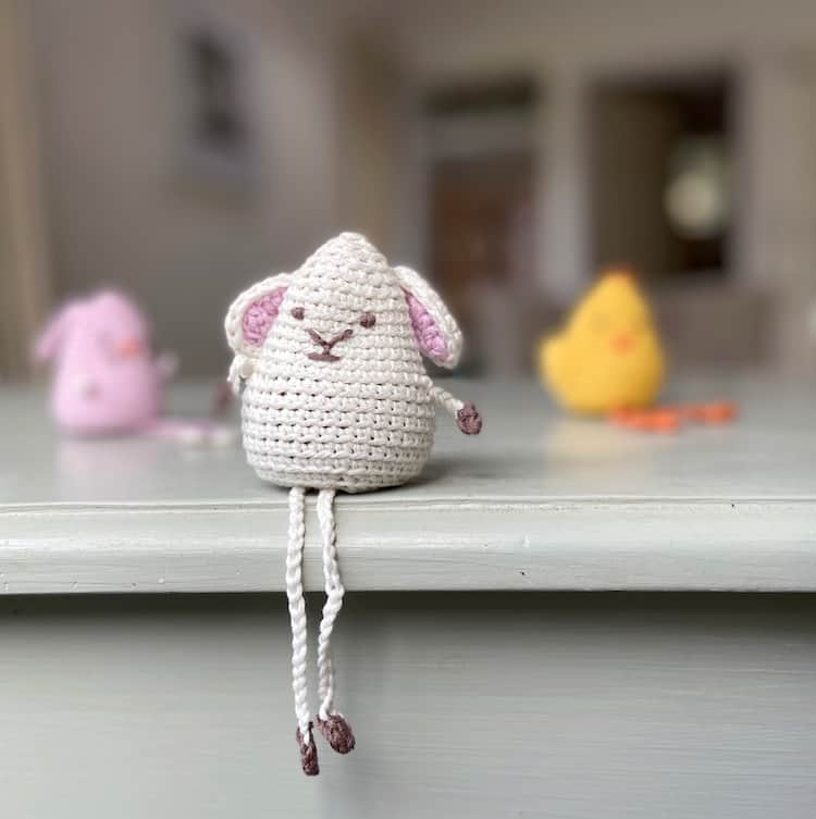 amigurumi crochet lamb toy sitting on edge of shelf