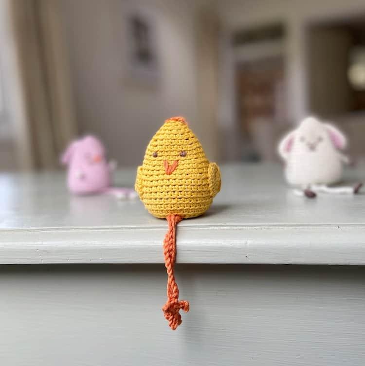 amigurumi crochet chick toy sitting with crossed legs on edge of shelf