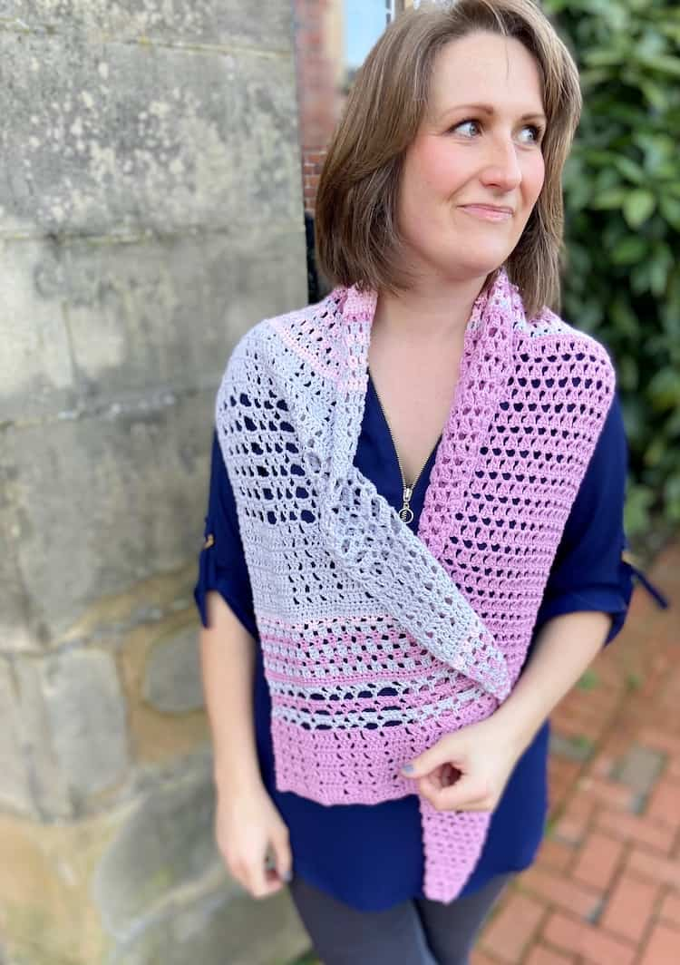 woman looking sideways wearing pink and grey lace crochet shawl wrapped loosely around shoulders