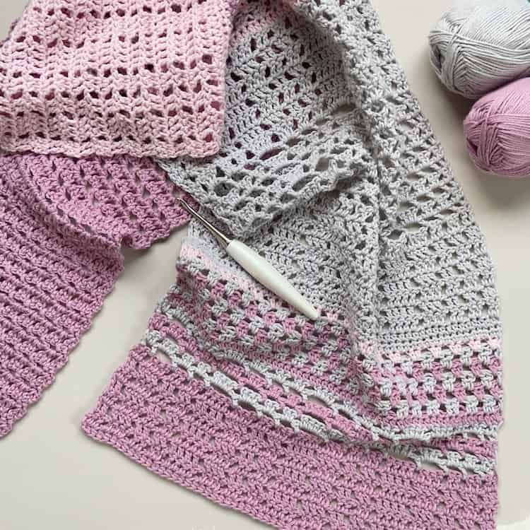 flatlay image of pink and grey summer lace crochet shawl with crochet hook and yarn