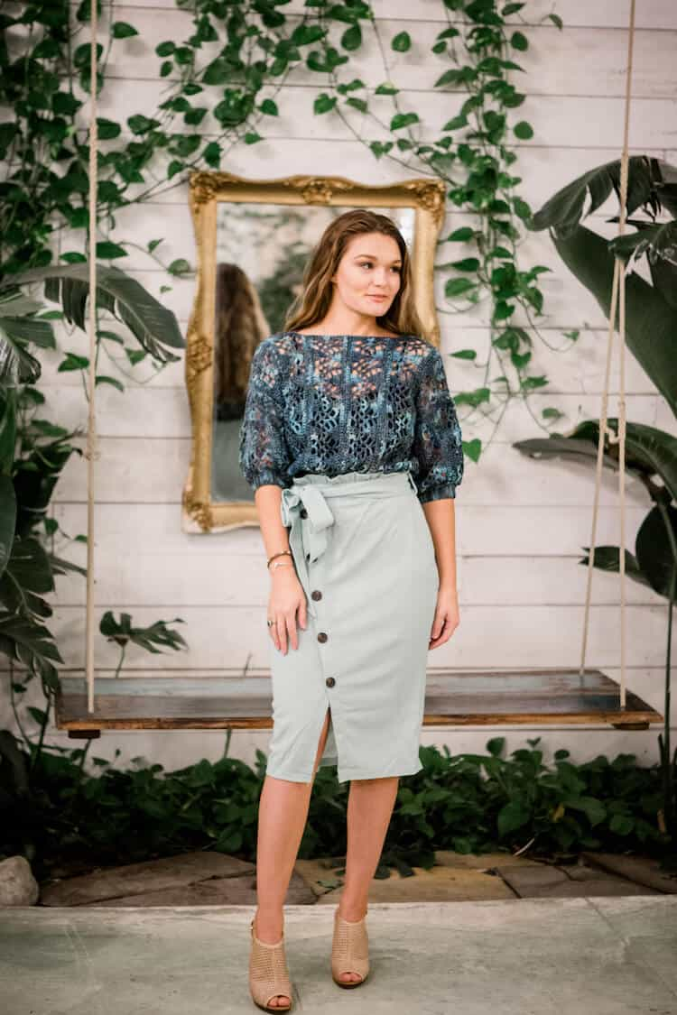 woman in tropical hot house wearing 3/4 sleeve lace crochet top and light green skirt