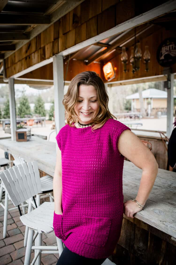 woman looking down, leaning on bar wearing bright pink crochet dress with pockets