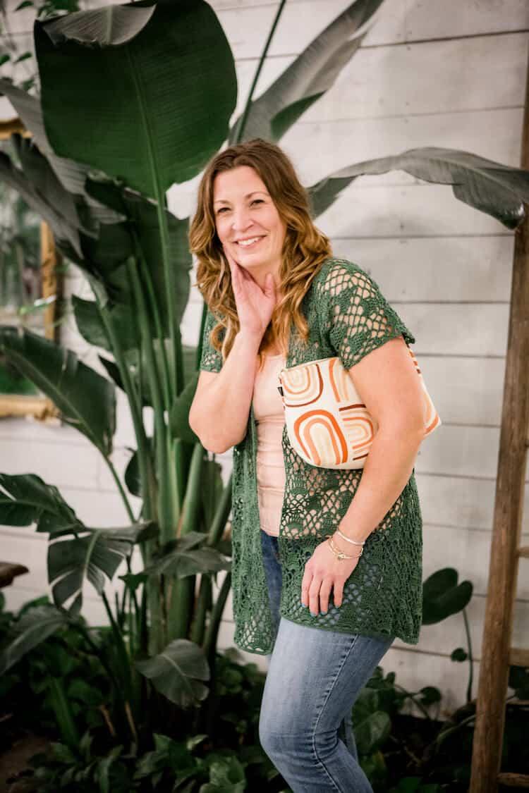 woman with clutch handbag under arm wearing green lace crochet cardigan