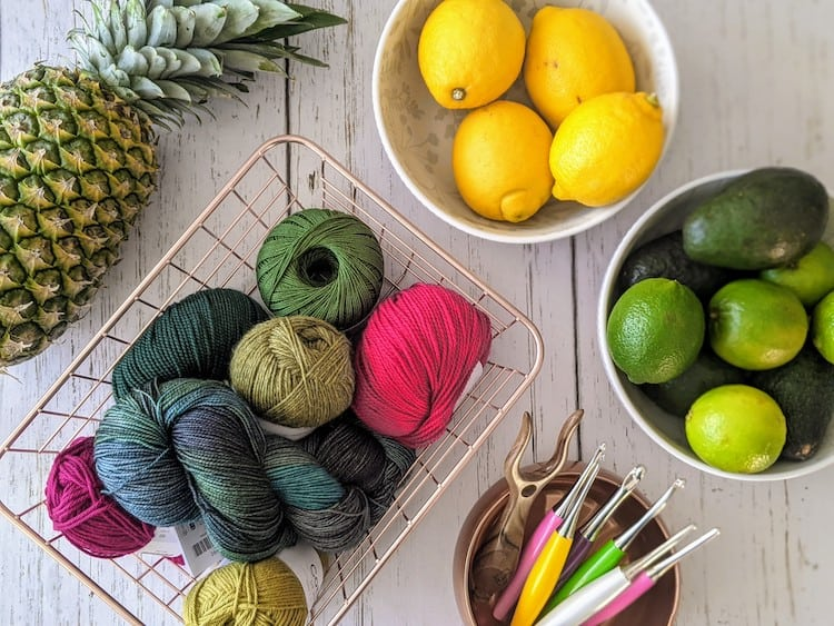 basket of pink and green yarn with crochet hooks surrounded by bowls of lemons, limes and a pineapple