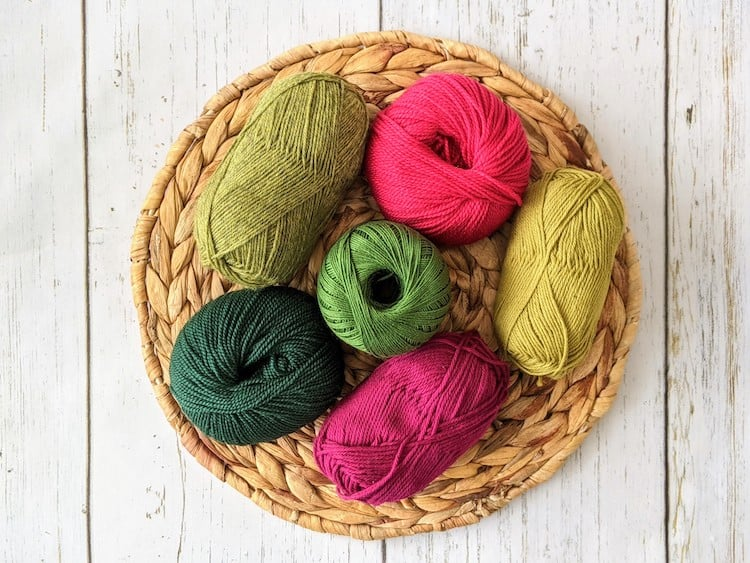 6 balls of pink and green yarn sitting on woven mat on table