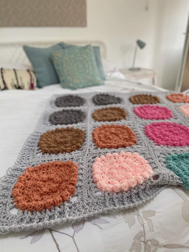 colourful and modern crochet blanket laying on a bed