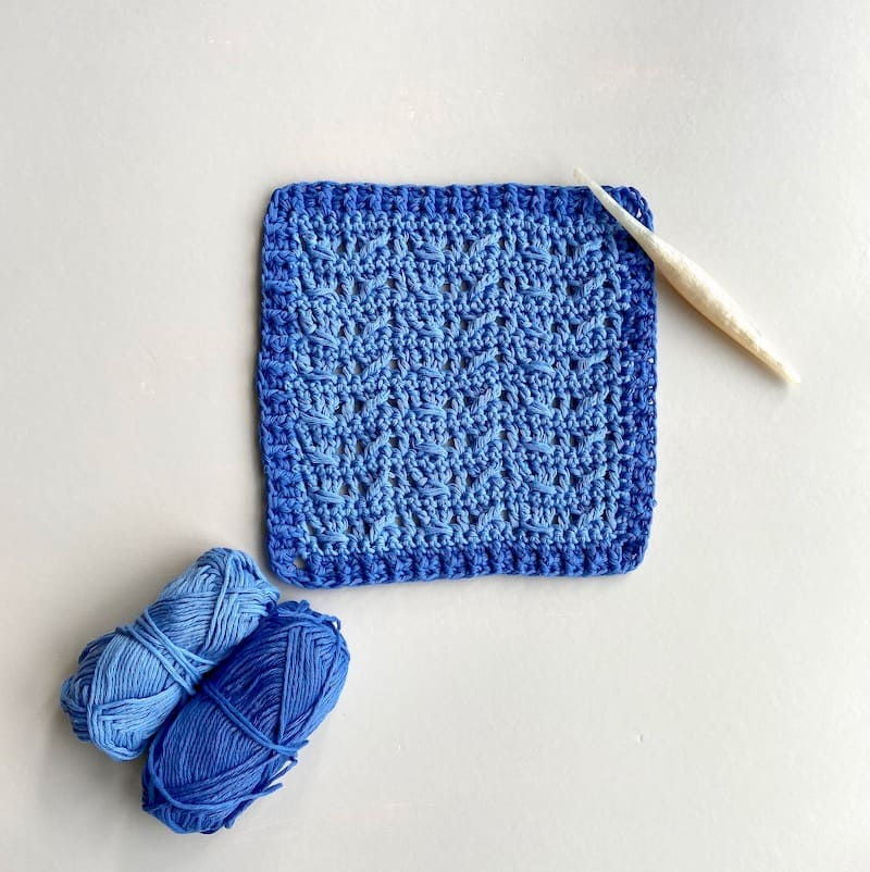 light and dark blue crochet cable stitch square with white crochet hook