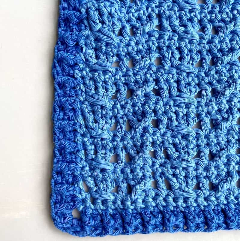 close up of crochet cable stitch pattern in blue cotton yarn