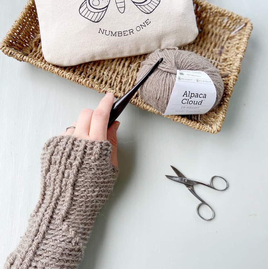 left hand wearing crochet mitten holding a crochet hook with scissors, yarn and canvas pouch on desk