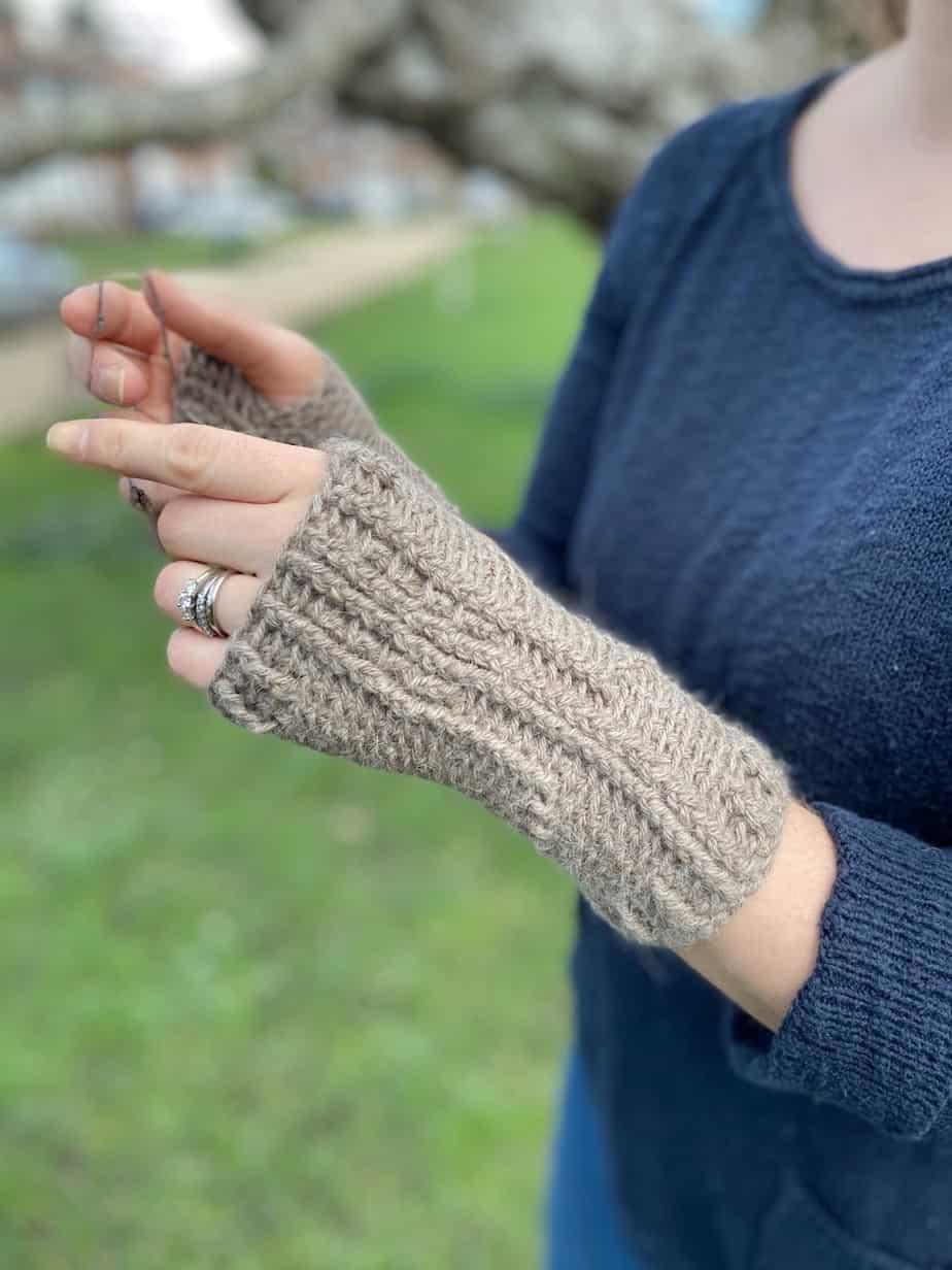 woman wearing fingerless crochet wool mitts in beige brown colour