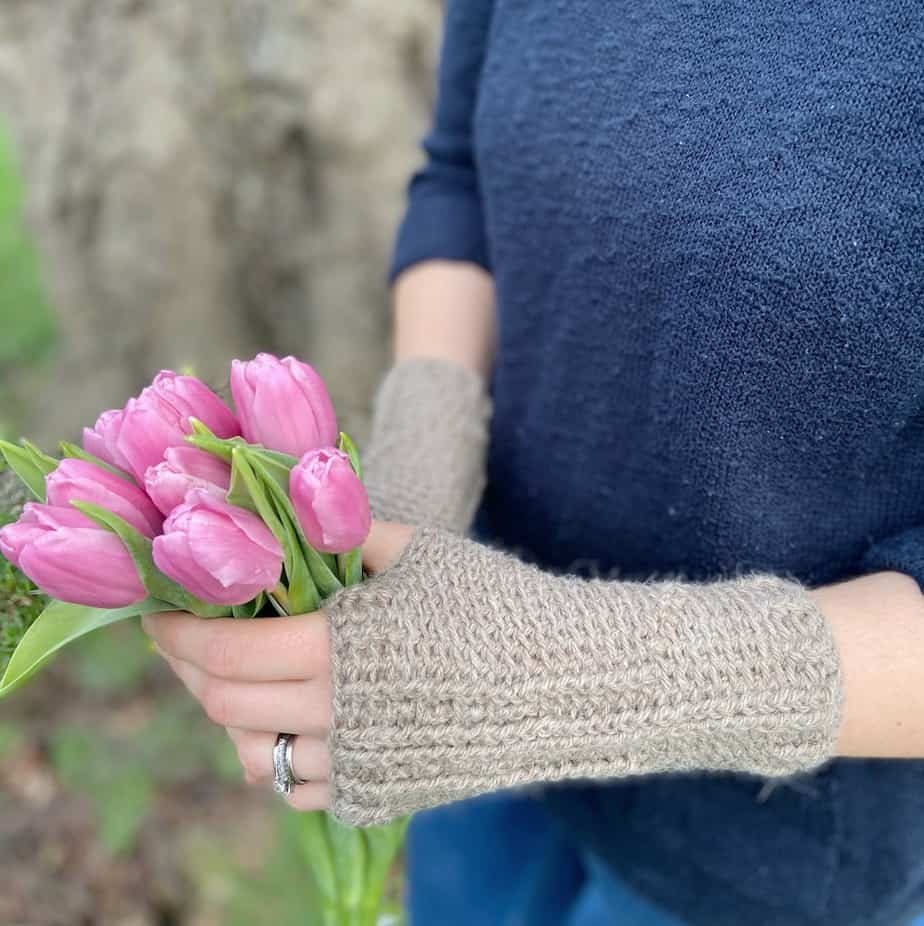Person wearing beige brown crochet hand warmers holding a bunch of pink tulips