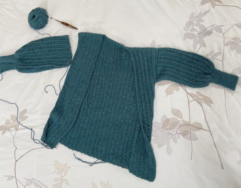 a knit-look crochet cardigan laid flat on a bed with crochet hook and yarn, one sleeve hasn't been joined yet.