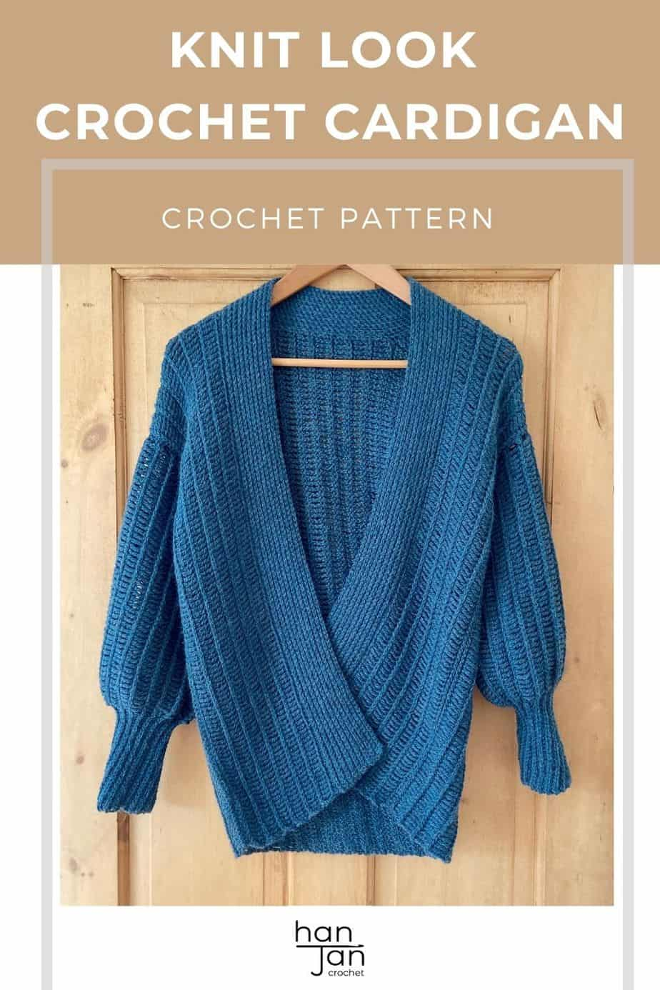 knit-look crochet cardigan hanging on a pine door. It has balloon sleeves and a ribbed collar.