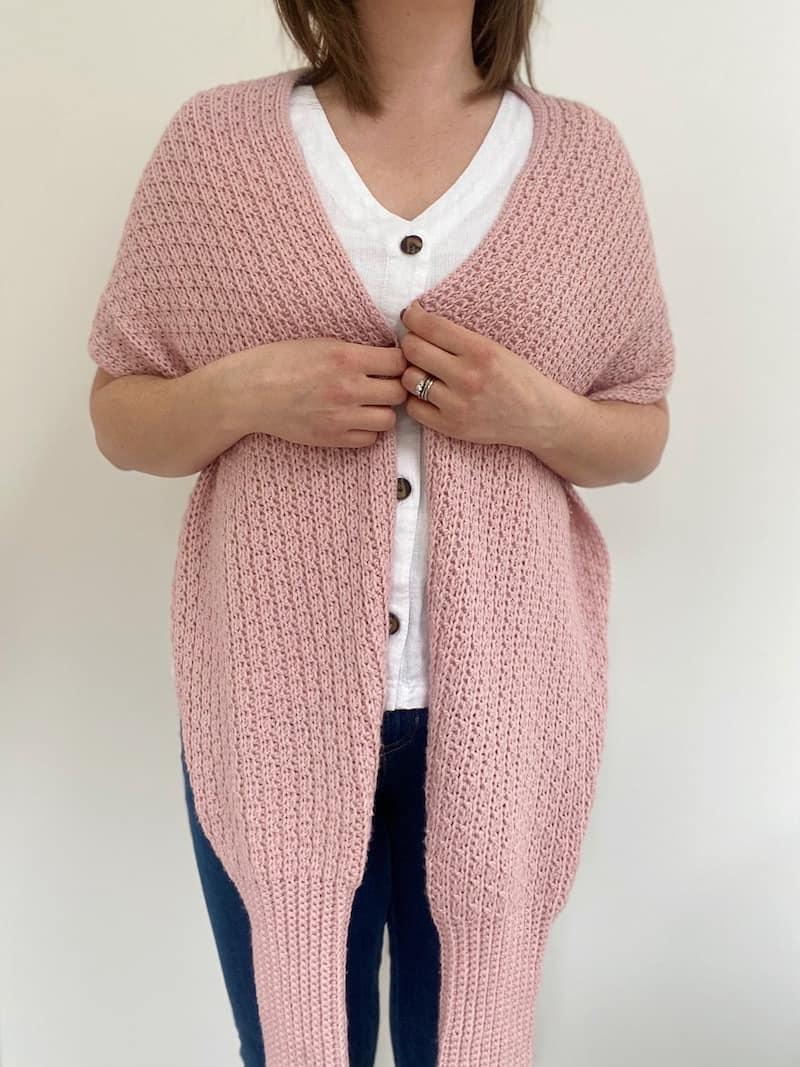 woman wearing pink crochet scarf draped around neck
