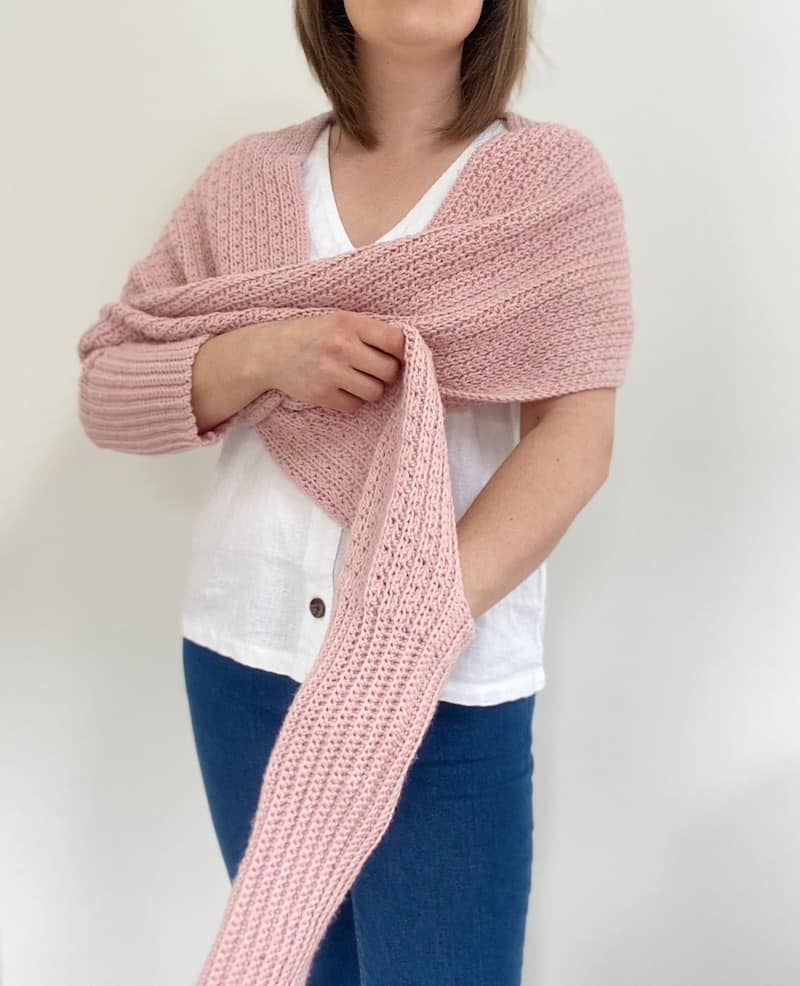 woman putting arm through sleeve of pink scarf with sleeves crochet pattern