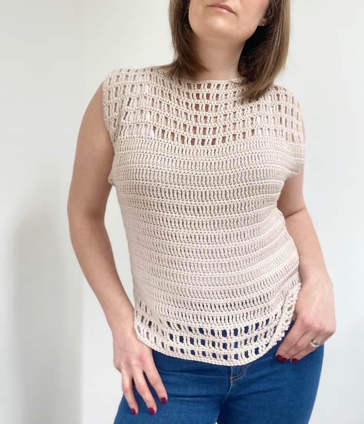 woman looking down wearing cream lace crochet summer top